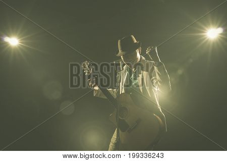 Asian Musician singing a song and playing the guitar which have a microphone on black background with spot light and lens flare musical concept