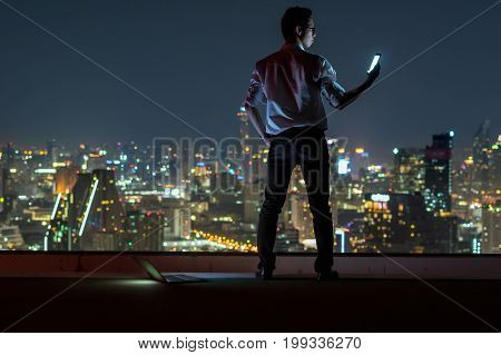 Asian businessman standing and using the smart mobile phone over the cityscape background at night time Business success and technology concept