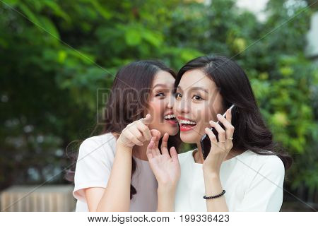 Young Woman Whispering Into Cheerful Friend's Ear While On Call