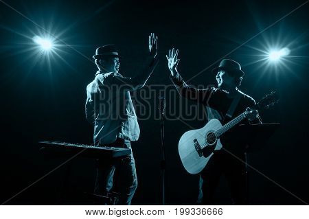 Musician Duo band playing on black background with spot light and lens flare musical concept