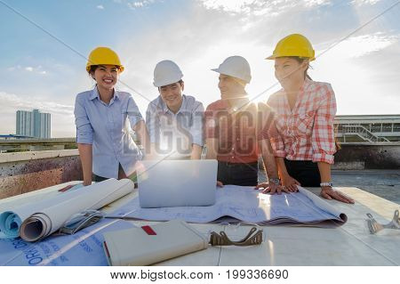 Happy professional construction engineers working with Corporate Colleagues Teamwork and equipment such as blueprint Safety glasses and technology laptop on the table at the sunset with lens flare