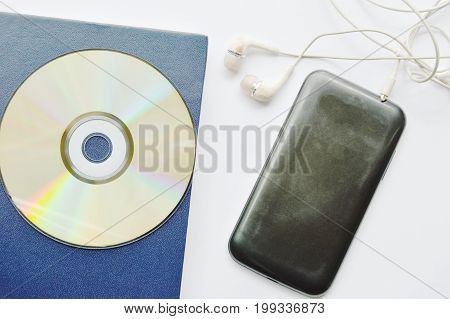 book and CD- rom with earphones connect in smartphone on white background