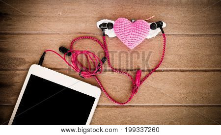 Portable audio earphones with tablets and heart Crochet on wood background vintage color tone
