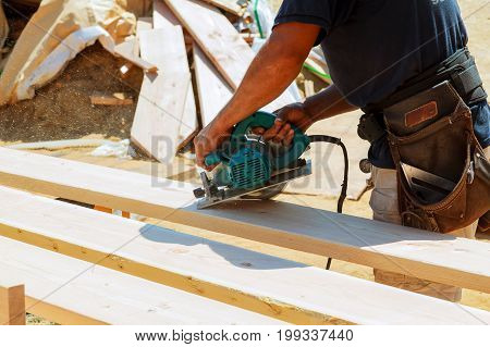 Carpenter Using Circular Saw For Cutting Wooden Boards. Construction Details Of Male Worker Or Handy