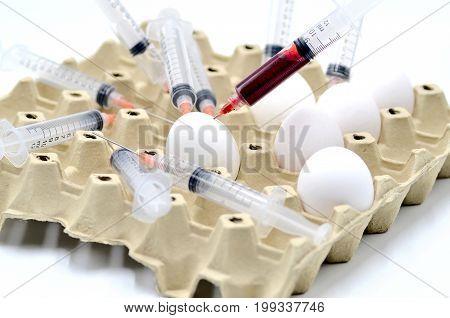 Eggs and syringe on white background photo
