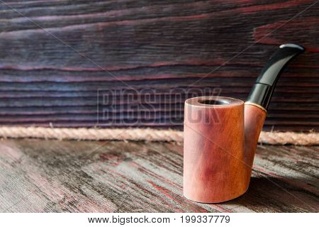 Smoking pipe on a background of mahogany.