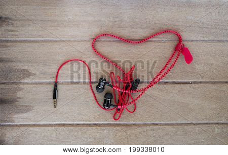 Portable audio earphones with heart Crochet on wood background