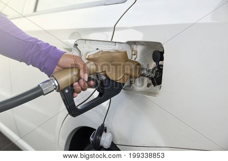 Hand hold Fuel nozzle to add fuel in car at filling station