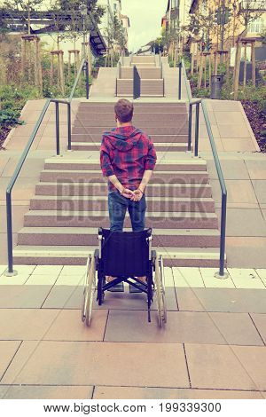 Man Standing With Wheelchair In Front Of Stairs