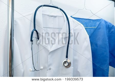 white and blue medical occupation uniforms on hanger