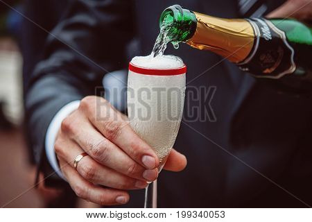 Pouring champagne into glass at wedding, close up