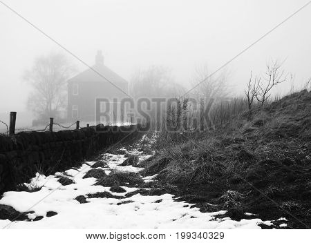 country path in heavy fog with snow a wall and trees and house visible though the mist