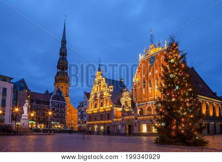 RIGA, LATVIA - 25 DEC 2015. Illuminated City Hall Square with House of the Blackheads and Saint Peter church in Old Town