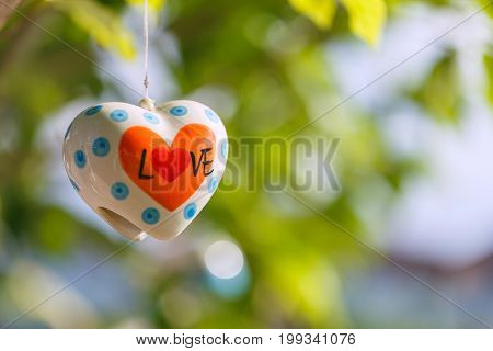 Shape of heart and word LOVE with green bokeh background.