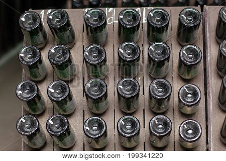 Rectangular, regular arrangement of bottles of champagne in the production of wine, a direct frontal view of the bottom of the green bottles.