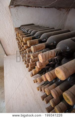 Many bottles - lie one above the other, in a niche in the cellar. Bottle with a wooden stopper and covered with dust. Excerpt going - secondary fermentation.