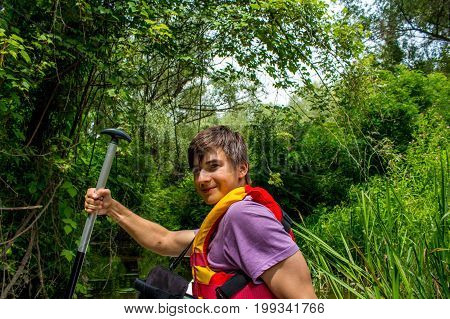 A young handsome man kayaking in a forest on a stream among lianas and smiling