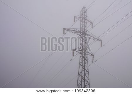 electric pylon and power line in morning fog. Dim world in obscure.