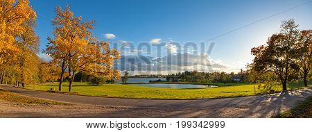 The road in the shade of the autumn trees - on the banks of the pond