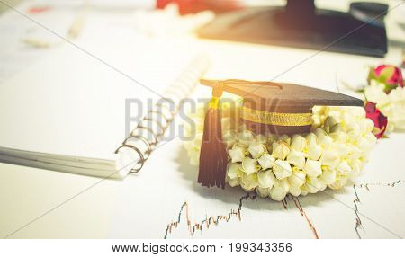 Concept of congratulate graduate study success graduation black cap on Jasmine garland Education certificate of Abroad international university diploma or certificate.