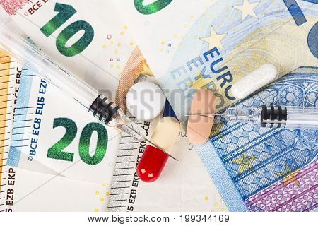Several pills and syringes on euro banknotes bills close-up. White background. Pharmacy and drug cost economy