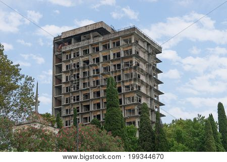 the destroyed building of the sanatorium of the Soviet period among lush subtropical vegetation a bright summer day