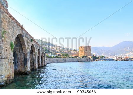 Old shipyard as part of Alanya fortress with red tower background in Alanya, Turkey