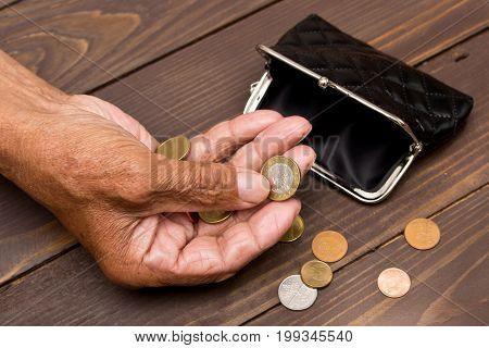 Coins in the hands of an elderly man and an empty black wallet on wooden background. The concept of poverty in retirement.