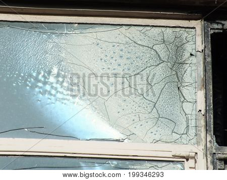 broken window with cracks in a derelict abandoned house partly melted by fire