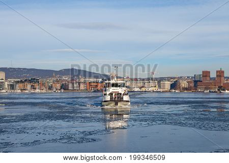 OSLO, NORWAY - 27 FEB 2016: City ferry sevice Oslo X and view of the Aker Brygge, modern part of Oslo. Marina and buildings.