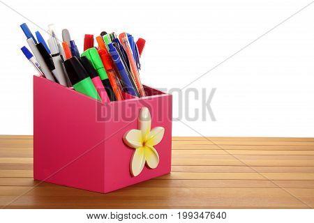Ballpoint Pens in Holder on Wooden Background