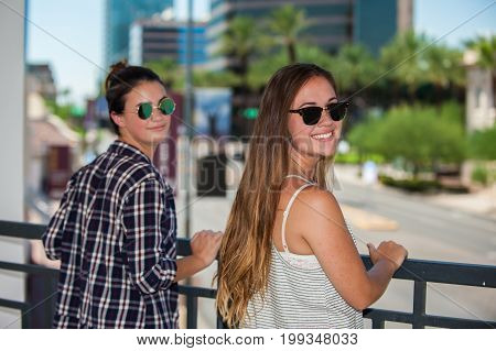 Sisters looking over Phoenix downtown streets while leaning on handrail.