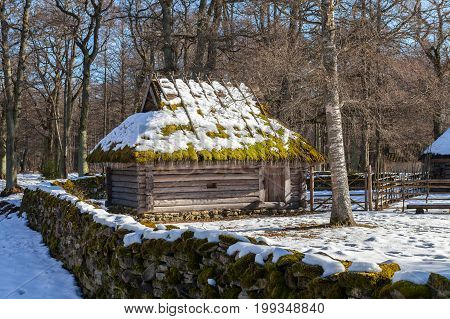 Rustic barn in the yard with stoned fence. Traditional Estonian style.