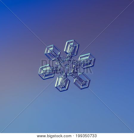 Real snowflake macro photo: large snow crystal with six simple, short and broad arms and small hexagonal center. Snowflake glittering on smooth blue gradient background in cold light.
