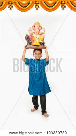 Portrait of cute little Indian boy holding a Ganesh idol or lord ganesha or ganapati murti /statue over his head, taking home on Ganesh Chaturthi, Isolated over white background