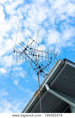television antenna on roof with blue sky
