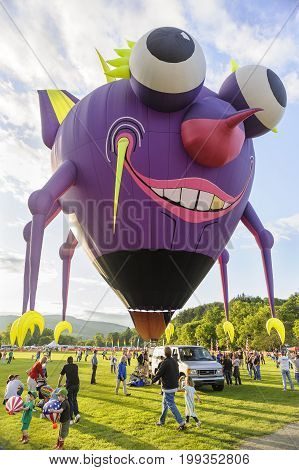 Quechee Vermont USA - June 19 2009: The Flying Purple People Eater hot air balloon grinning at the crowd at the Quechee Hot Air Balloon Craft and Music Festival