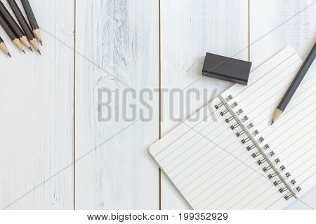 Notebook pencil and eraser on wooden table Top view Concept of workplace equipment illustration office supplies background