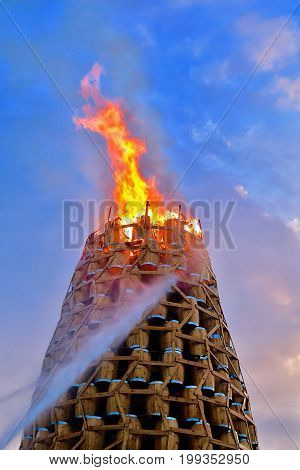 Midsummer festival fire at the harbour in Bergen, Norway. Barrel tower burning from top to bottom. Water is squirted to control the fire. Old custom.