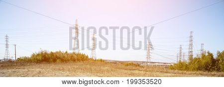 Power line in nature with sun light wide screen Technology and nature concept