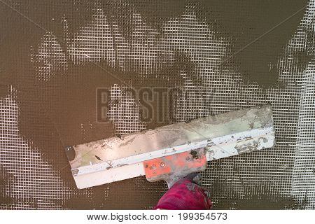 Plastering the wall with a spatula working process close-up