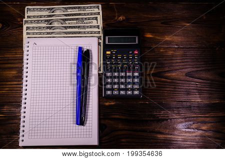 Notepad, Pen, Calculator And Dollar Bills On Wooden Table. Top View