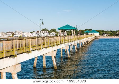 HAMPTON, VIRGINIA - JULY 9, 2017:  Fisherman on the 709-foot fishing pier at Buckroe Beach.  Originally the site of a plantation in 1619, Buckroe Beach now includes a beach, pier and public park.
