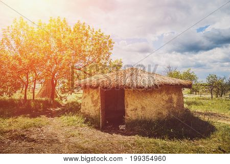 Old round house with thatched roof in sunlight, rural landscape
