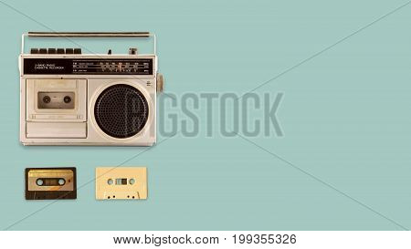 Radio cassette recorder and player with music tape cassette on color background. retro technology. flat lay top view hero header. vintage color styles.