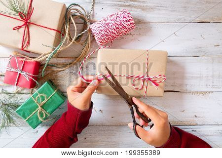 Girl hands wrapping gift for Christmas presents and New Year. Craft and handmade present gift boxes. Creative Flat lay and top view composition.