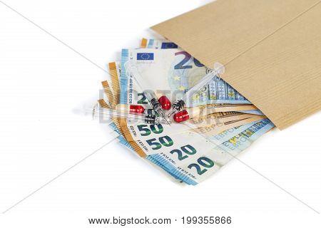 Syringes and euros banknotes bills in brown envelope. Cost of health medicine traffic of drug. Close-up.