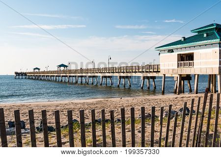 HAMPTON, VIRGINIA - JULY 9, 2017:  The Buckroe Beach fishing pier, located on the site of a former plantation.  The area is now a popular tourist attraction for the beach, fishing and public park.