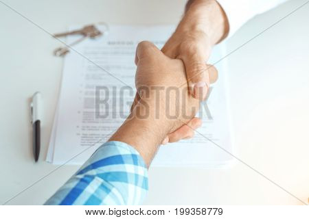 Man with real estate agent rent apartment handshake