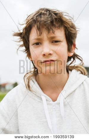 outdoor portrait of teen school boy looking straight into camera on natural background, casual lifestyle image